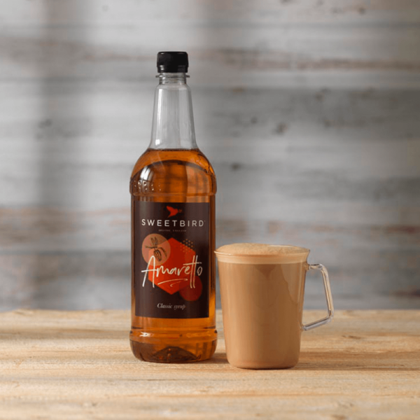 Bottle of sweet bird amaretto syrup with hot beverage beside