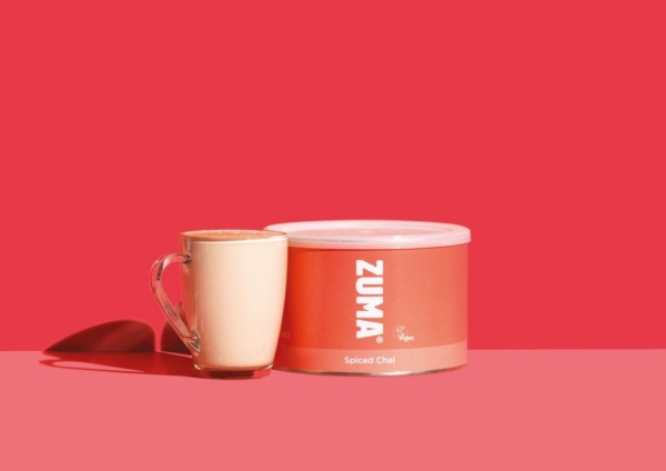 Tin of zuma spiced chai with drink on red background