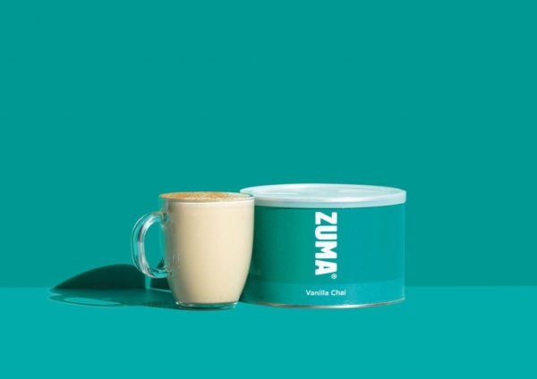 Tin of zuma vanilla chai with drink on teal background