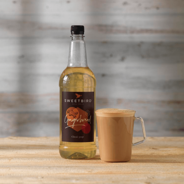 bottle of sweet bird gingerbread syrup with hot beverage beside