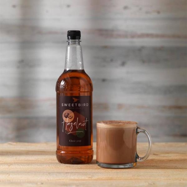 bottle of sweet bird hazelnut syrup with hot beverage beside