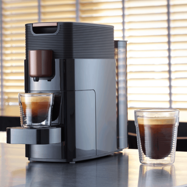 KFEE One pod coffee machine pouring a drink in a home setting