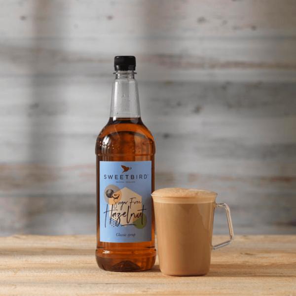 bottle of sugar free hazelnut syrup with hot beverage beside