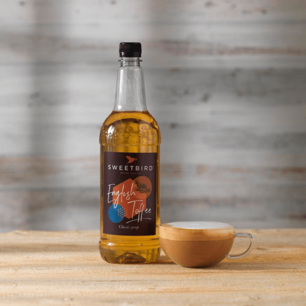 Bottle of sweetbird English toffee syrup with hot beverage beside