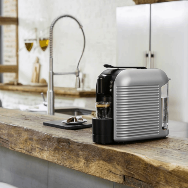 KFee Wave pod coffee machine pouring a drink in a home setting