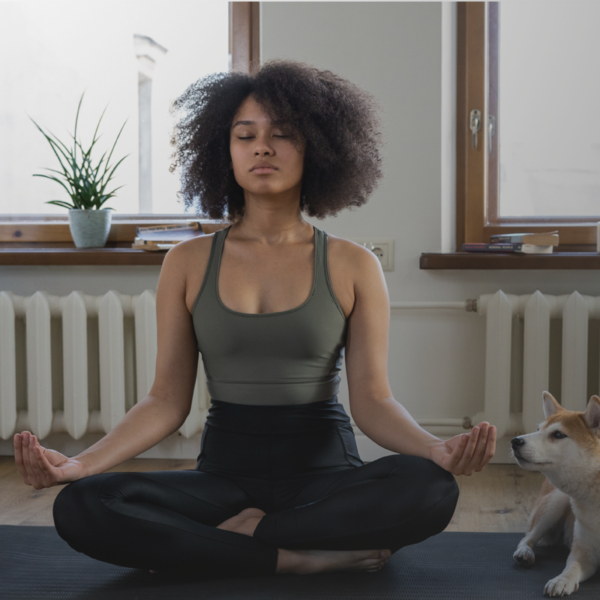 Lady practicing yoga with pet dog