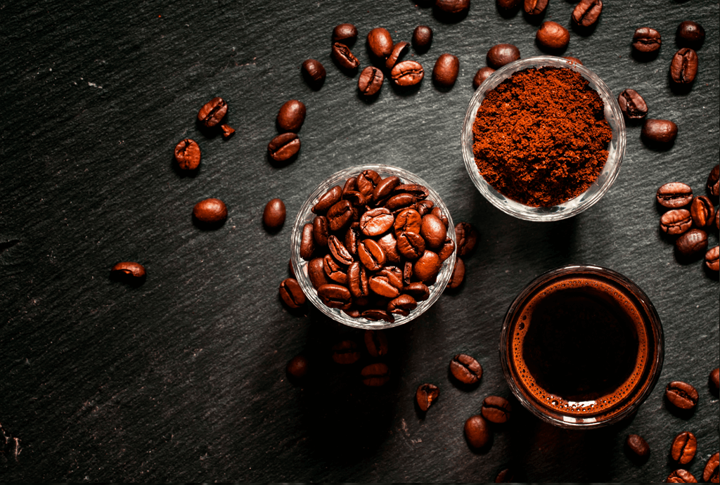 Ground coffee and whole beans on slate background