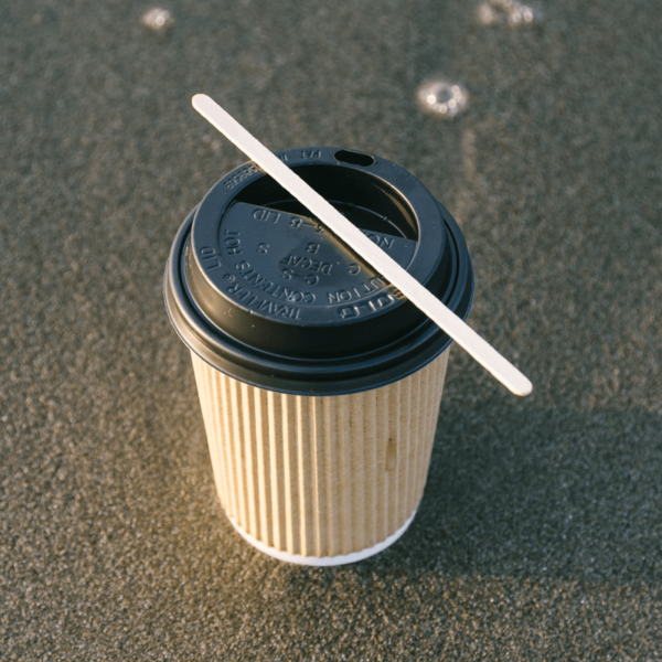 Wooden drinks stirrer on top of cup