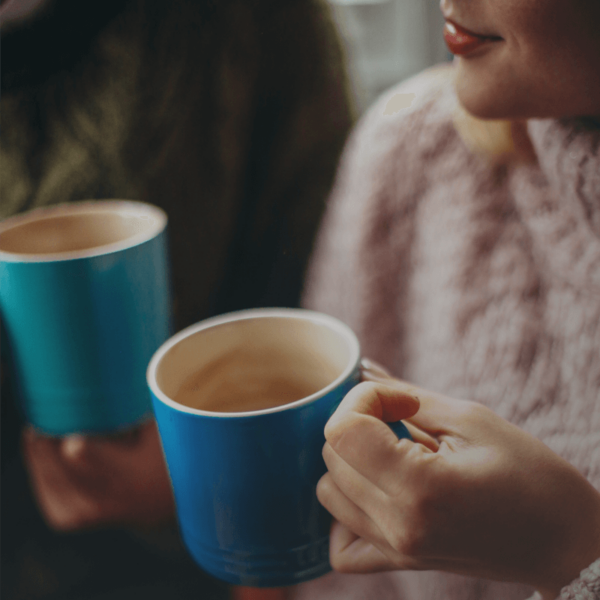 Two people with blue mugs enjoying cafe submit decaf coffee