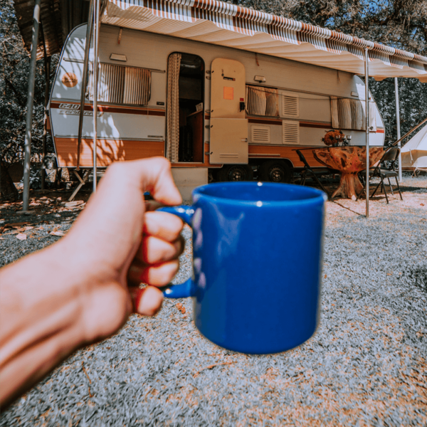 Person holding mug of coffee made with Lavazz decaf coffee beans in front of caravan