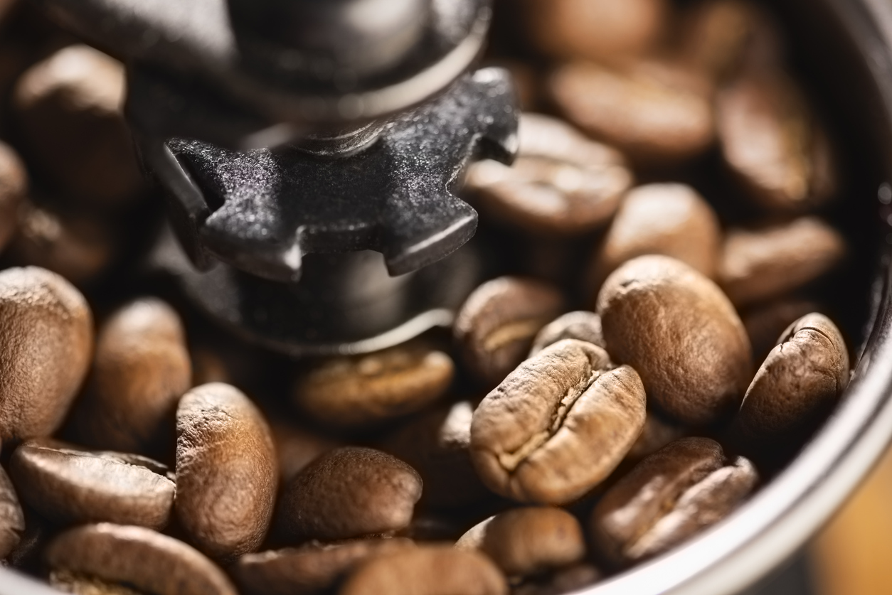 close-up image of whole coffee beans inside a manual coffee grinder